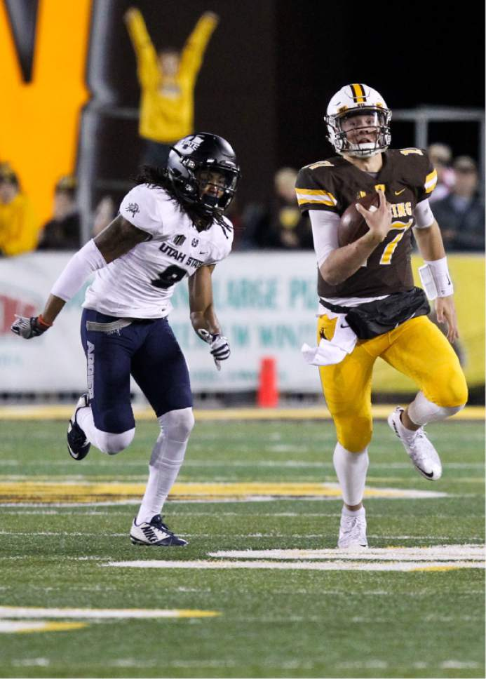 Wyoming quarterback Josh Allen runs down the field as Utah State cornerback Wesley Bailey attempts a tackle during the second half of an NCAA college football game in Laramie, Wyo., Saturday, Nov. 5, 2016. (AP Photo/Shannon Broderick)
