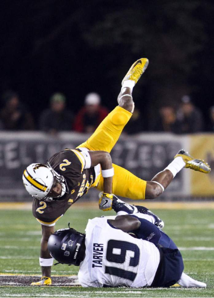 Wyoming cornerback Robert Priester jumps over Utah State wide receiver Ron'Quavion Tarver during the second half of an NCAA college football game in Laramie, Wyo., Saturday, Nov. 5, 2016. (AP Photo/Shannon Broderick)
