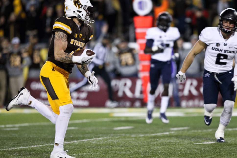 Wyoming's Tanner Gentry runs down the field on his way to score a touchdown as Utah State's Dallin Leavitt attempts to stop him during the first half of an NCAA college football game in Laramie, Wyo., Saturday, Nov. 5, 2016. (AP Photo/Shannon Broderick)