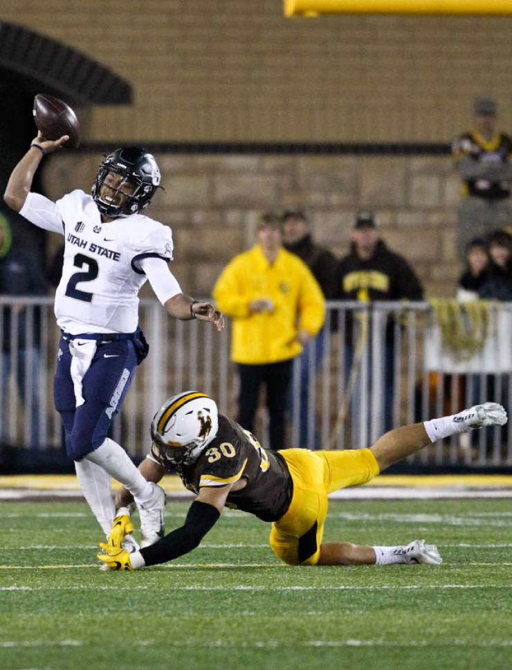 Utah State quarterback Kent Myers throws the ball as he is tackled by Wyoming linebacker Logan Wilson during the second half of an NCAA college football game in Laramie, Wyo., Saturday, Nov.5, 2016. (AP Photo/Shannon Broderick)