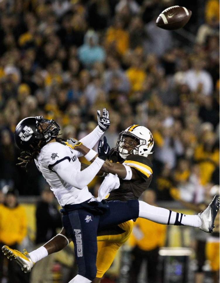 Utah State wide receiver Alex Byers is tackled by Wyoming cornerback Robert Priester as he attempts to make a catch during the second half of an NCAA college football game in Laramie, Wyo., Saturday, Nov. 5, 2016. (AP Photo/Shannon Broderick)