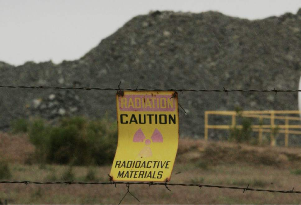 Blanding, UT.    A caution sign on a fence in front of ore from the Pandora Mine outside La Sal that is piled before processing at the White Mesa Mill outside Balnding, Utah. 5/23/07  Jim Urquhart/Salt Lake Tribune
