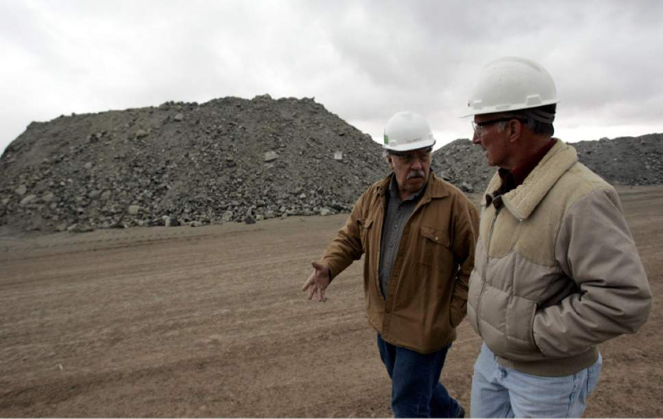 Tribune file photo  With piles of uranium ore behind them, Rich Bartlett, left, and Harold Roberts discuss the operations of the White Mesa mill that processes uranium outside Blanding, Utah, in this May 23, 2007 file photo.