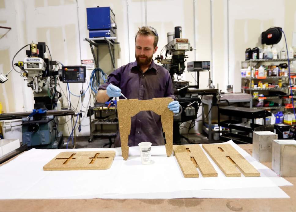 "In this Tuesday, Sept. 27, 2016 photo, prototype engineer Kenneth Lush assembles a stool at Ecovative Design in Green Island, N.Y. Ecovative Design is a business staking its growth on mycelium, the thread-like ""roots"" of mushrooms. The mycelium grows around small pieces of stalks and stems to create a bound-together material that can be molded into soft packaging for glassware or pressed into the boards used for the footstools they recently began selling. (AP Photo/Mike Groll)"