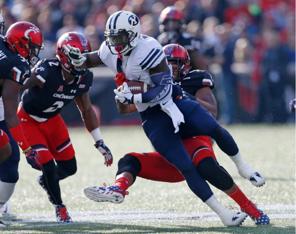 Brigham Young running back Jamaal Williams, front, is tackled by Cincinnati defensive end Bryan Wright, rear, during the first half of an NCAA college football game, Saturday, Nov. 5, 2016, in Cincinnati. (AP Photo/Gary Landers)