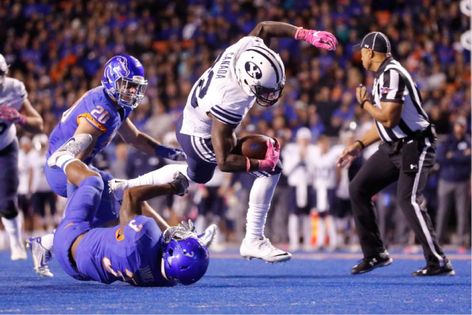 BYU running back Squally Canada (22) is tripped up by Boise State safety Chanceller James (3) during the second half of an NCAA college football game in Boise, Idaho, Thursday, Oct. 20, 2016. Boise State won 28-27. (AP Photo/Otto Kitsinger)