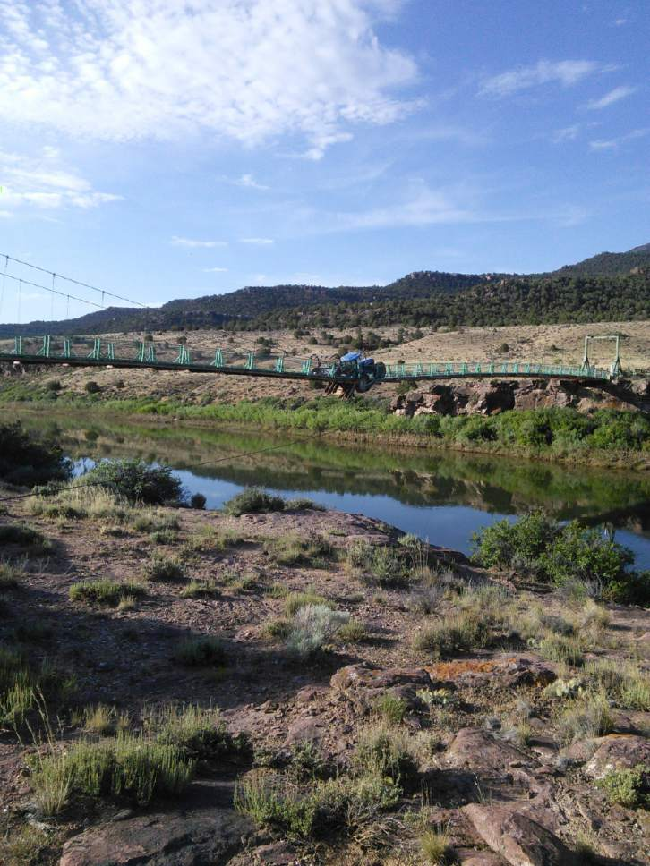 Courtesy  |  U.S. Fish and Wildlife Service  Utah officials want to help pay for the reconstruction of Browns Park Swinging Bridge just inside Colorado. Among the West's last surviving swinging bridges, it was rendered unusable in 2014 when a tractor broke through its decking.