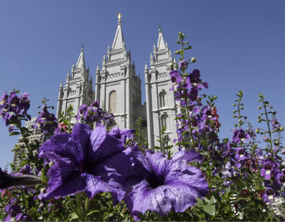 FILE - In this Sept. 3, 2014, file photo, shows flowers blooming in front of the Salt Lake Temple in Temple Square, in Salt Lake City. (AP Photo/Rick Bowmer, File)