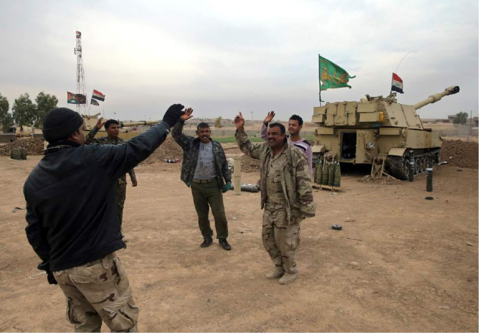 Iraqi army soldiers from the Ninth Armored Division, 109th artillery battalion, stand in front their 155mm mobile artillery unit, as they shout slogans and celebrate after they received informaiton that their shell accurately hit an Islamic State militants target, at Ali Rash village east of Mosul, Iraq, Tuesday, Nov. 15, 2016. Iraq launched a major offensive last month to drive IS out of the northern city, the country's second largest, which is still home to more than 1 million civilians. (AP Photo/Hussein Malla)