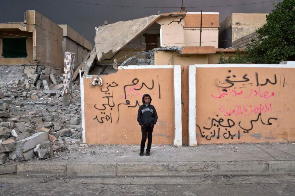 FILE - In this Thursday, Nov. 10, 2016, file photo, a boy stands by a house that belonged to an Islamic State militant in Qayara, some 50 kilometers south of Mosul, Iraq. When Iraqi forces drove Islamic State militants from the town of Qayara in August, it was hailed as an early triumph over the extremists. But the government has failed to restore lost services, violent revenge attacks persist, and some residents are bitter and angry. (AP Photo/Marko Drobnjakovic)