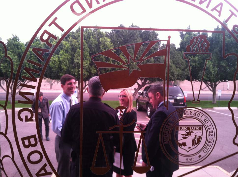 Nate Carlisle   The Salt Lake Tribune  Colorado City, Ariz., attorneys Jeff Matura, left, and Melissa England, speak with Scottsdale, Ariz., Police Chief Alan Rodbell, foreground, and Hildale, Utah, attorney Blake Hamilton on Nov. 16, 2016, in Phoenix. The attorneys attended a meeting of the Arizona Police Officer Standards and Training Board. The board opted to start discipline proceedings against the marshals from Hildale and Colorado City.