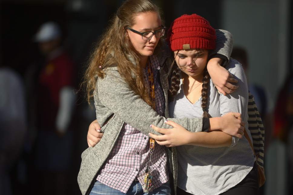 Trent Nelson | The Salt Lake Tribune  Mountain View students Holly Hilton (left) and Albany Cox hug outside the high school on Tuesday, Nov. 15 2016, where police say a 16-year-old boy stabbed five other boys before stabbing himself. The alleged stabber is in police custody.