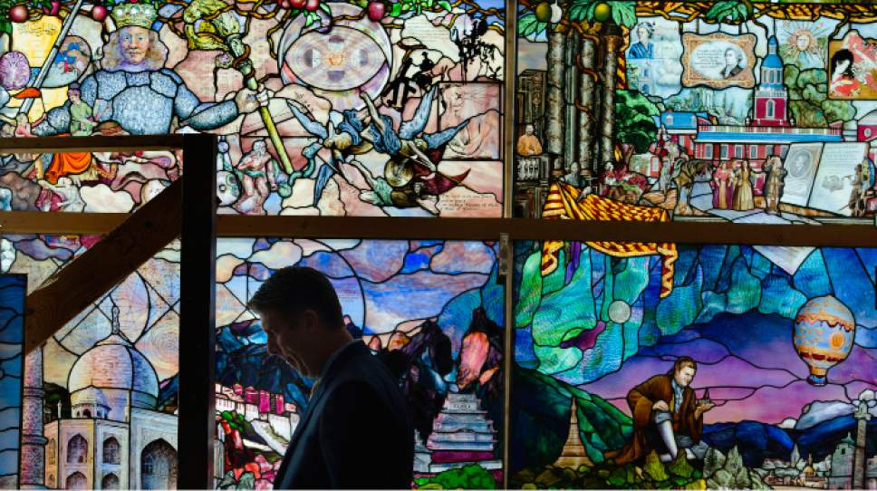 Steve Griffin | The Salt Lake Tribune   UVU President Matthew Holland walks in front of a stained glass panel at the Holdman Studios where the installation is being created, in Lehi, on Monday, Oct. 10, 2016. To celebrate its 75th anniversary, Utah Valley University has commissioned the major stained glass art installation called the Roots of Knowledge.