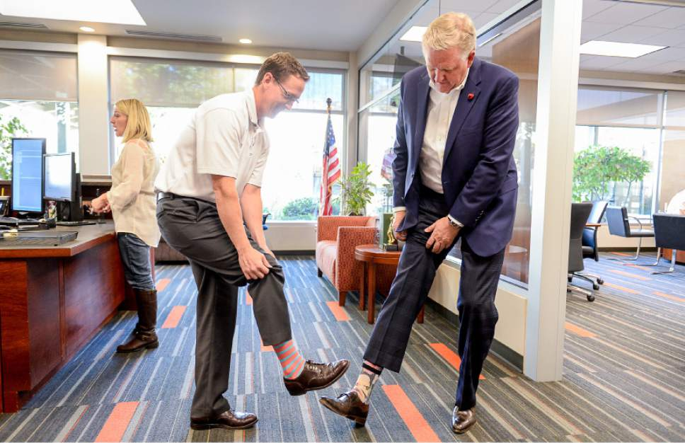Francisco Kjolseth | The Salt Lake Tribune Bryan Hall, left, with Prestige Financial, compares socks with his boss CEO Bryant Henrie during a recent tour of the credit financing company in Salt Lake City, a firm universally praised by its employees as a great place to work.