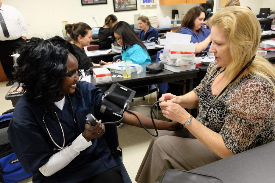 Francisco Kjolseth | The Salt Lake Tribune Working on her associates degree in Medical Specialties, Jemima Sebit, left, is guided through the process of taking vital signs with a stethoscope by instructor Elsa Pool at Stevens-Henager College in Murray.