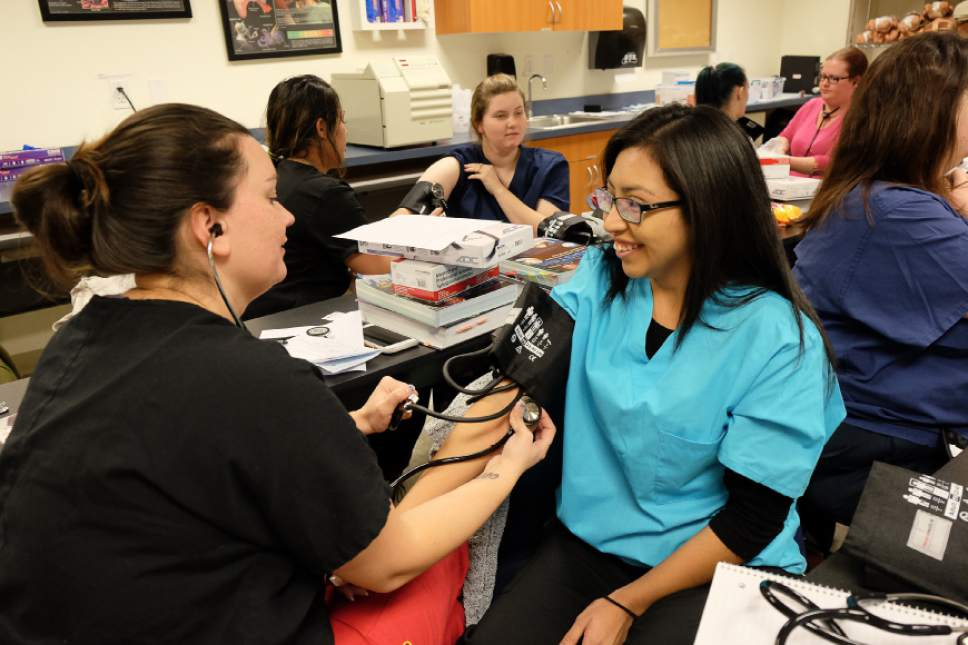 Francisco Kjolseth | The Salt Lake Tribune Working on their associates degree in Medical Specialties, Brandy Miera, left, and Berenice Mireles learn how to take vital signs with stethoscopes during a class at Stevens-Henager College in Murray.