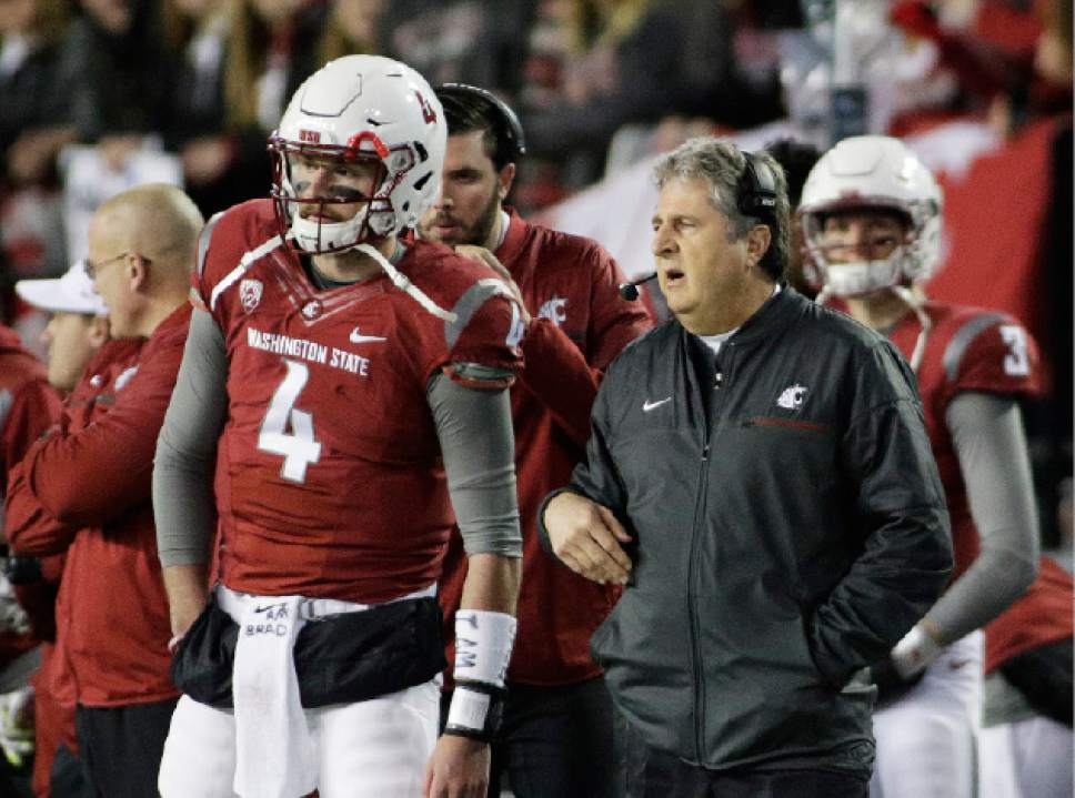 Washington State coach Mike Leach, right, speaks with quarterback Luke Falk (4) during the first half of an NCAA college football game against California in Pullman, Wash., Saturday, Nov. 12, 2016. (AP Photo/Young Kwak)
