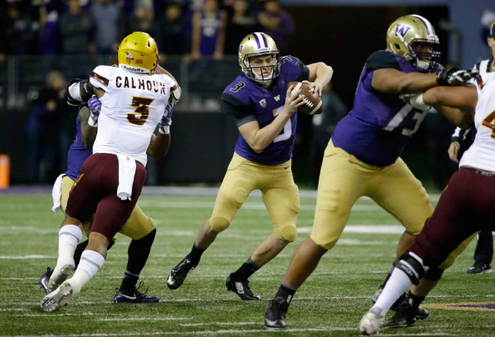Washington quarterback Jake Browning, center, tries to escape from pressure by Arizona State linebacker DJ Calhoun, left, in the first half of an NCAA college football game, Saturday, Nov. 19, 2016, in Seattle. (AP Photo/Ted S. Warren)