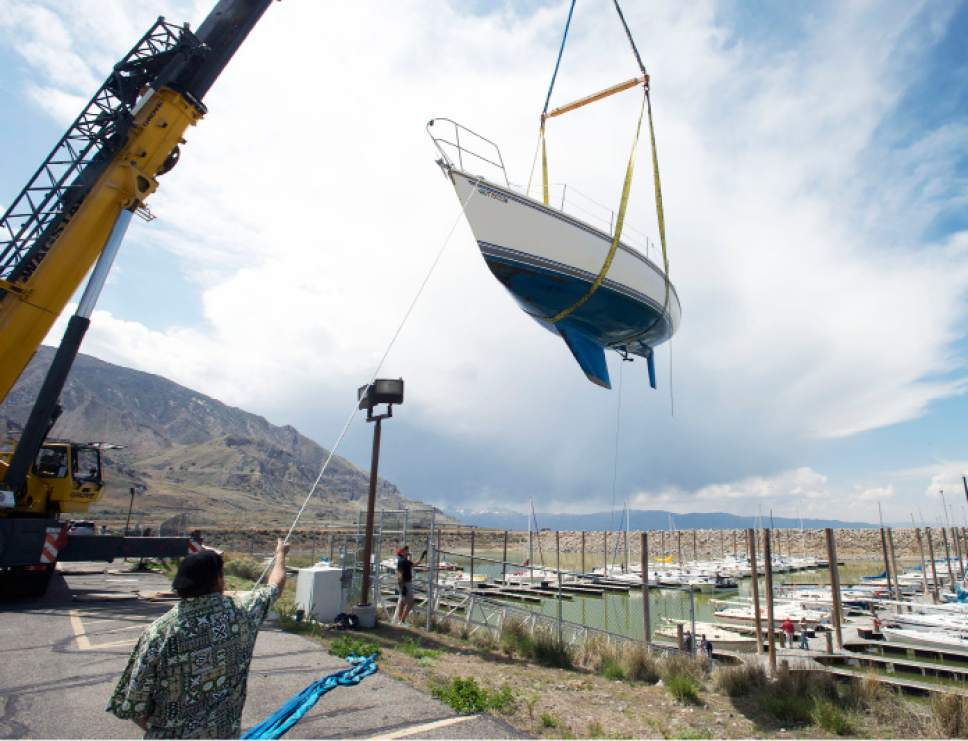 Steve Griffin  |  The Salt Lake Tribune  A crane lifts a sailboat from its slip at the Great Salt Lake State Marina in Salt Lake City, Thursday, April 23, 2015. This time of year sailboats usually are put in, but this time about 80 boats are scheduled to be pulled out in the face of dropping lake levels that threaten to render the marina unusable for sailing.