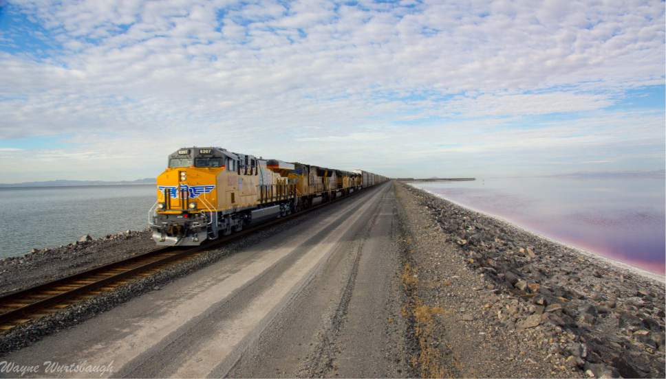 Wayne Wurtsbaugh  | Courtesy of  Utah State University A Union Pacific train traverses the rock causeway crossing the north end of Utahís Great Salt Lake. Since 1959 this causeway has isolated the hyper-saline North Arm, the reddish water on the right, from the rest of the lake to the south. Utah and federal regulators are now weighing the railroadís plan to construct a 150-foot breach and bridge that would allow water to travel back and forth. Without such mixing, the lakeís overseers fear the South Arm could experience swings in its salt load to the detriment of industries and tiny organisms that depend on the lake.
