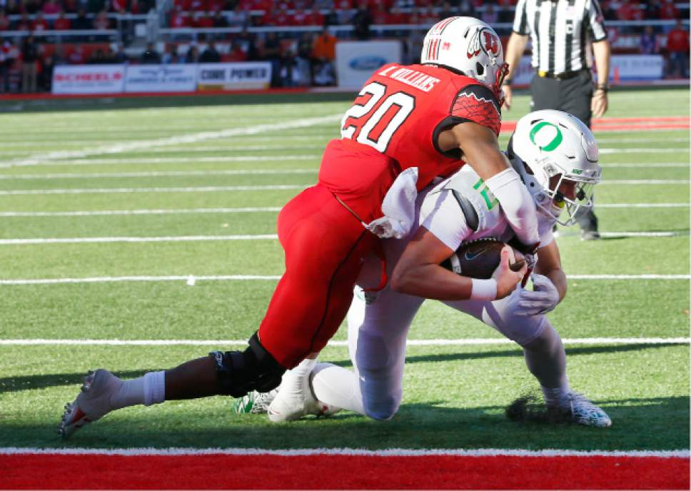 Oregon quarterback Justin Herbert (10), scores a touchdown as Utah defensive back Marcus Williams (20) tries to tackle him in the second half of an NCAA college football game, Saturday, Nov. 19, 2016, in Salt Lake City. (AP Photo/George Frey)