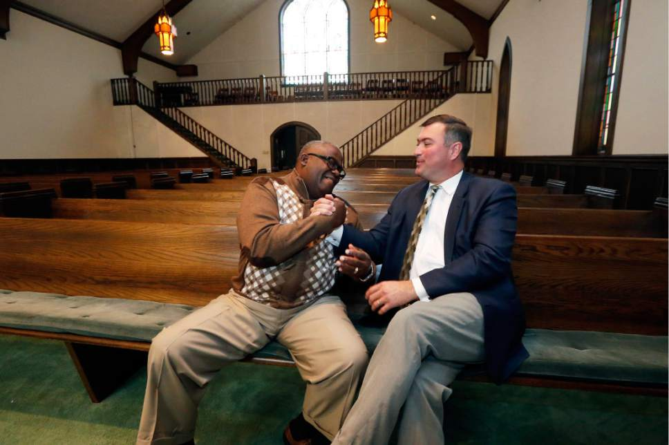 """Bishop Clarence Green, overseer of Hopewell Missionary Baptist Church, left, and Pastor James Nichols of the First Baptist Church of Greenville join hands inside the chapel that First Baptist offered as a temporary home for the members of Hopewell, Tuesday, Nov 22, 2016, in Greenville, Miss. Hopewell was burned three weeks ago and spray-painted with """"Vote Trump."""" An investigation into the cause of the fire continues. (AP Photo/Rogelio V. Solis)"""