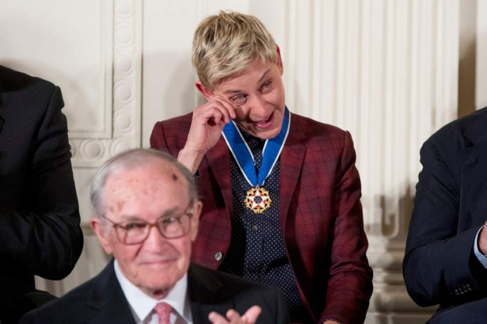Actress, comedian, and talk show host Ellen DeGeneres, center, wipes a tear from her eye after receiving the Presidential Medal of Freedom from President Barack Obama during a ceremony in the East Room of the White House, Tuesday, Nov. 22, 2016, in Washington. (AP Photo/Andrew Harnik)