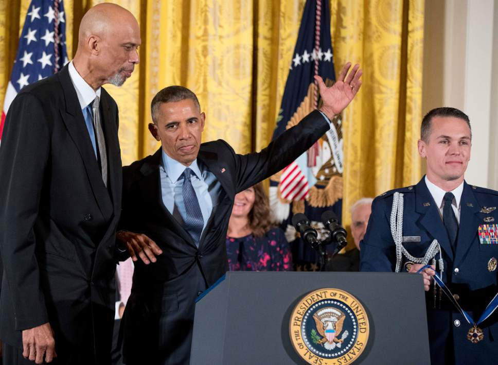 President Barack Obama, second from left, pretends to shoot an imaginary basketball over former NBA basketball player Kareem Abdul Jabbar, left, as he presents the Presidential Medal of Freedom during a ceremony in the East Room of the White House, Tuesday, Nov. 22, 2016, in Washington. Obama is recognizing 21 Americans with the nation's highest civilian award, including giants of the entertainment industry, sports legends, activists and innovators. (AP Photo/Andrew Harnik)