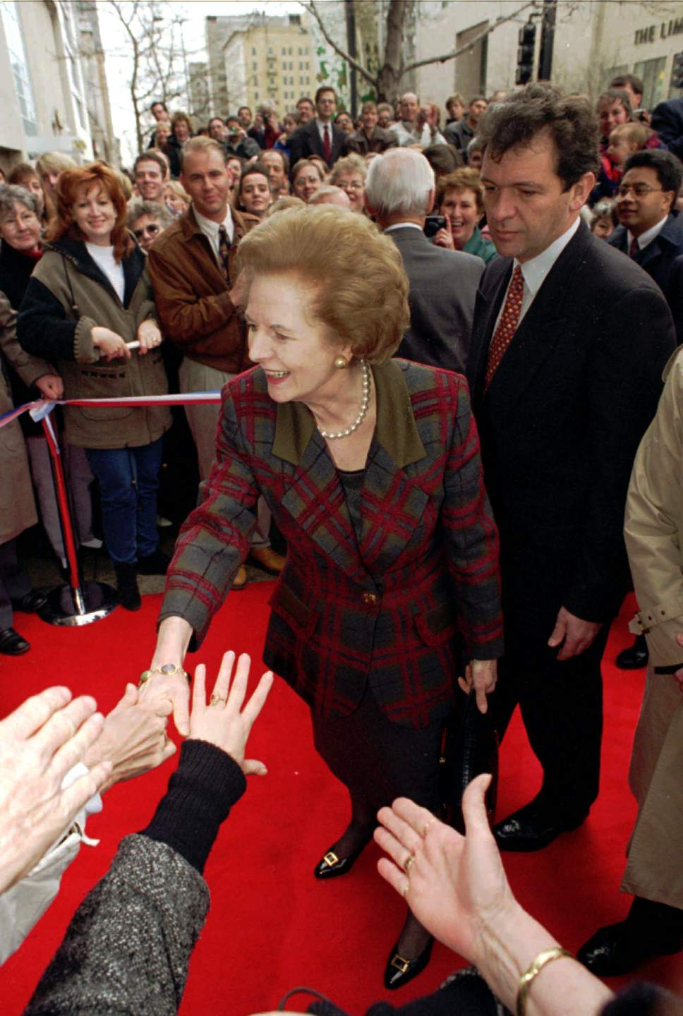 Fans reach out to touch Lady Margaret Thatcher as she arrives outside the ZCMI department store during ribbon cutting ceremony to start out the UK/Utah Festival Monday, March 4, 1996 in Salt Lake City. The former British Prime Minister is in the city for a week on a Utah/United Kingdom trade promotion. (AP Photo/Steve C. Wilson)