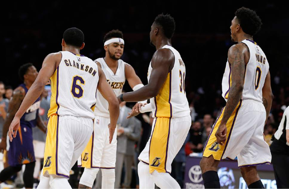 Los Angeles Lakers guard Jordan Clarkson (6), forward Julius Randle (30), and guard Nick Young (0) gets congratulations from guard D'Angelo Russell, second from left, during the second half of an NBA basketball game in Los Angeles, Sunday, Nov. 6, 2016. The Lakers won 119-108. (AP Photo/Alex Gallardo)