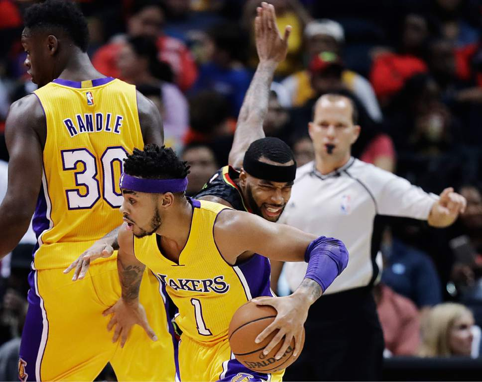 Los Angeles Lakers' D'Angelo Russell, center, dribbles as Atlanta Hawks' Malcolm Delaney, right, works through a pick set by Julius Randle during the first quarter of an NBA basketball game in Atlanta, Wednesday, Nov. 2, 2016. (AP Photo/David Goldman)