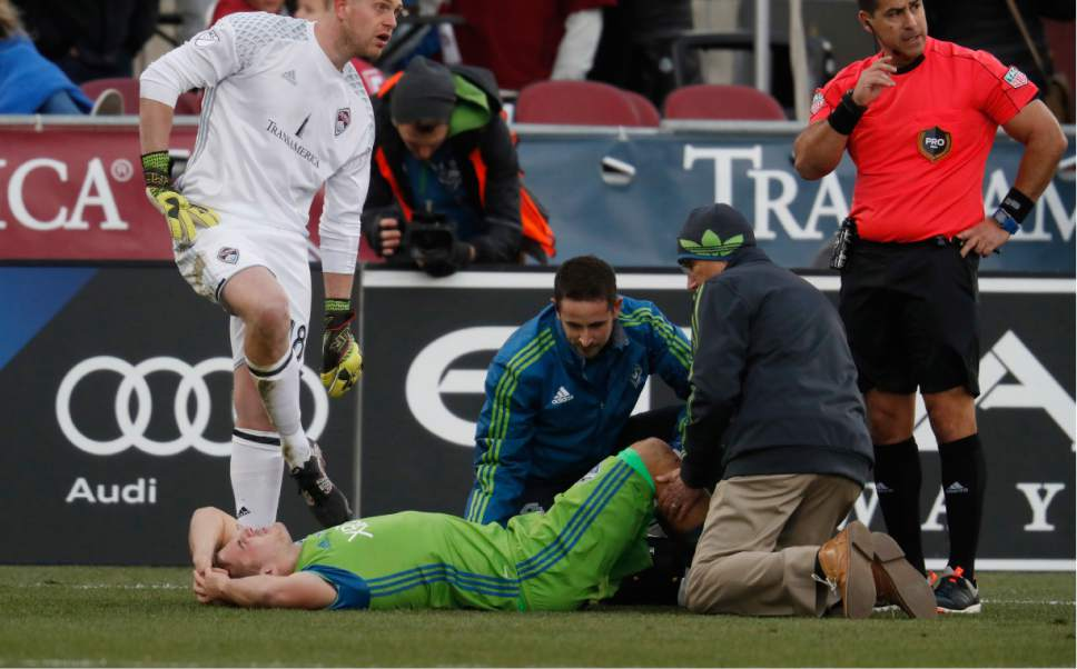 Seattle Sounders forward Jordan Morris, front left, is attended to by trainers, at right, as Colorado Rapids goalkeeper Zac MacMath, back left, looks on after Morris scored a goal but was slightly injured on the play in the second half of the second leg of an MLS Western Conference soccer finals game Sunday, Nov. 27, 2016, in Commerce City, Colo. Seattle won 1-0 to advance to the MLS championship game. Morris remained in the game. (AP Photo/David Zalubowski)
