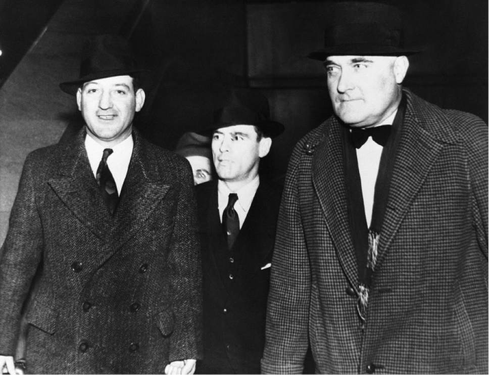 """John Paul Chase, center, companion of the slain """"Baby Face"""" Nelson, is shown March 28, 1935 as he left Chicago in the company of federal marshals to serve a life sentence in the Alcatraz Island prison for the slaying of federal agent Samuel Cowley. (AP Photo)"""