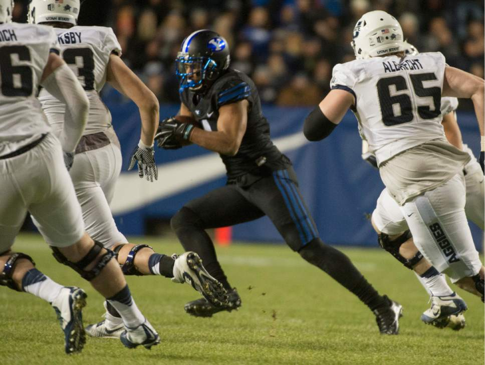 Rick Egan  |  Tribune file photo BYU linebacker Fred Warner, center, running back an interception against Utah State last season, is part of the linebacking corps that coach Kalani Sitake is loving this spring.