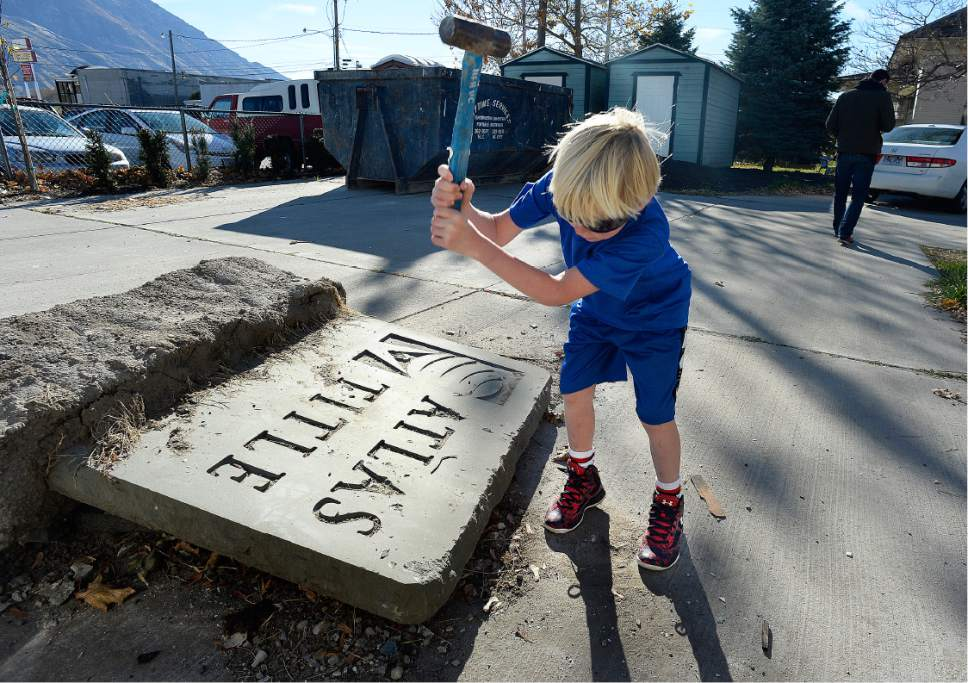 "Scott Sommerdorf   |  The Salt Lake Tribune   The old Atlas Title sign that was on the north side of the property is broken up during a work / cleanup day at the old Victorian home being renovated to house ""Encircle House"" which will be Provo's first LGBT resource center, Saturday November 19, 2016."