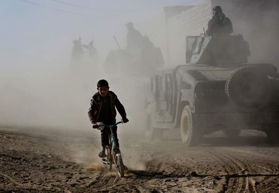 FILE - In this Nov. 23, 2016 file photo, an Iraqi boy rides his bicycle as he follows the special forces Humvees on their way to the front line to battle against Islamic State militants, in the Al-Samah neighborhood in Mosul, Iraq. Six weeks into the battle for Mosul, the Iraqi government's 50,000-strong expedition is a long way from finishing the job. The Islamic State is tenaciously defending its last major foothold in Iraq. A million civilians remain inside the city, preventing the use of overwhelming firepower. Iraqi commanders are alarmed that the progress has been lopsided. The battle-seasoned special forces are slowly advancing inside Mosul while other military outfits remain bogged down outside the city. (AP Photo/Hussein Malla, File)