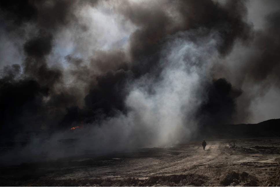 FILE - In this Nov. 22, 2016 file photo, an oil worker walks next to burning oil fields in Qayara, south of Mosul, Iraq. Six weeks into the battle for Mosul, the Iraqi government's 50,000-strong expedition is a long way from finishing the job. The Islamic State is tenaciously defending its last major foothold in Iraq. A million civilians remain inside the city, preventing the use of overwhelming firepower. Iraqi commanders are alarmed that the progress has been lopsided. The battle-seasoned special forces are slowly advancing inside Mosul while other military outfits remain bogged down outside the city.(AP Photo/Felipe Dana, File)