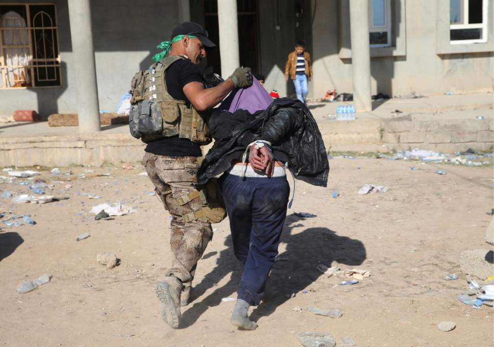 FILE - In this Nov. 24, 2016 file photo, an Iraqi special forces soldier carries an alleged Islamic State group collaborator to inside a house where they gather people to transfer them to refugee camps, in the Samah front line neighborhood, in Mosul, Iraq. Six weeks into the battle for Mosul, the Iraqi government's 50,000-strong expedition is a long way from finishing the job. The Islamic State is tenaciously defending its last major foothold in Iraq. A million civilians remain inside the city, preventing the use of overwhelming firepower. Iraqi commanders are alarmed that the progress has been lopsided. The battle-seasoned special forces are slowly advancing inside Mosul while other military outfits remain bogged down outside the city. (AP Photo/Hussein Malla, File)