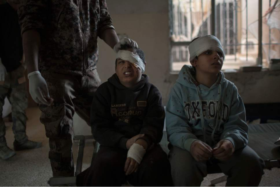 FILE - In this Nov. 25, 2016 file photo, brothers Taha, left, and Hasul are treated at a field hospital after being injured by a car bomb explosion during fighting between the Iraqi forces and Islamic State militants, in eastern Mosul, Iraq. Six weeks into the battle for Mosul, the Iraqi government's 50,000-strong expedition is a long way from finishing the job. The Islamic State is tenaciously defending its last major foothold in Iraq. A million civilians remain inside the city, preventing the use of overwhelming firepower. Iraqi commanders are alarmed that the progress has been lopsided. The battle-seasoned special forces are slowly advancing inside Mosul while other military outfits remain bogged down outside the city. (AP Photo/Felipe Dana, File)