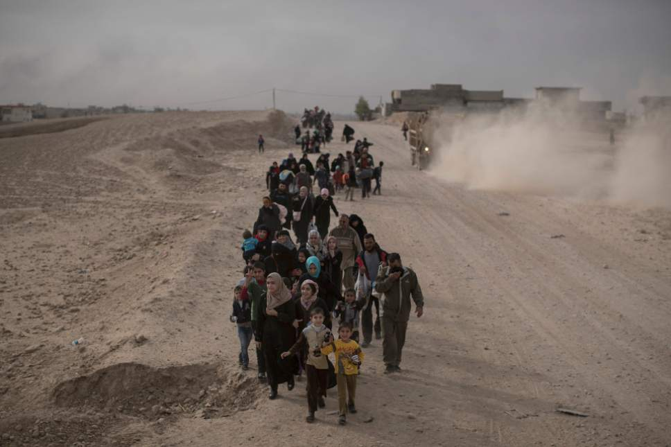 FILE - In this Nov. 15, 2016 file photo, internally displaced people flee fighting between Iraqi forces and Islamic State militants on a road in eastern Mosul, Iraq. Six weeks into the battle for Mosul, the Iraqi government's 50,000-strong expedition is a long way from finishing the job. The Islamic State is tenaciously defending its last major foothold in Iraq. A million civilians remain inside the city, preventing the use of overwhelming firepower. Iraqi commanders are alarmed that the progress has been lopsided. The battle-seasoned special forces are slowly advancing inside Mosul while other military outfits remain bogged down outside the city. (AP Photo/Felipe Dana, File)