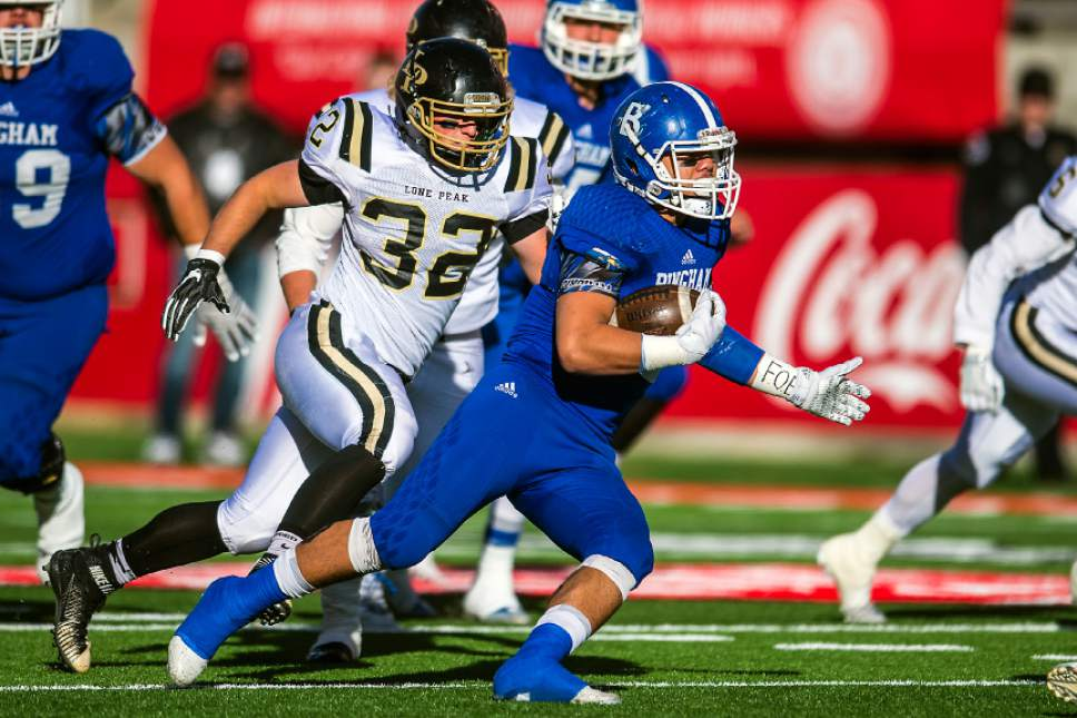 Chris Detrick  |  The Salt Lake Tribune Bingham's Amoni Kaili (32) runs past Lone Peak's Seth Larsen (32) during the 5A football championship at Rice-Eccles Stadium Friday November 18, 2016.