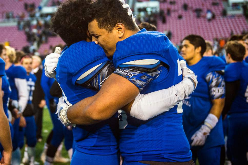 Chris Detrick  |  The Salt Lake Tribune Bingham's Tongi Langi (10) and Bingham's Jay Tufele (78) hug after winning the 5A football championship at Rice-Eccles Stadium Friday November 18, 2016. Bingham defeated Lone Peak 17-10.