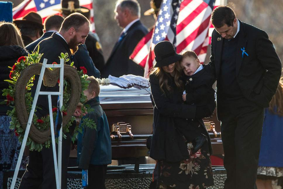 Chris Detrick  |  The Salt Lake Tribune Janica Ellsworth holds her son Oliver during the burial of Utah Highway Patrol Trooper Eric Ellsworth at Brigham City Cemetery Wednesday November 30, 2016. Ellsworth was hit by a car on the night of November 18, 2016 while trying to alert the driver of a semitrailer truck to go around a downed power line in Box Elder County. He died four days later.