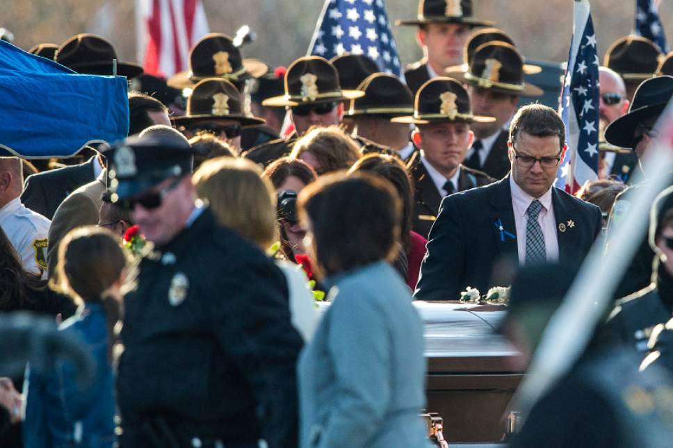 Chris Detrick  |  The Salt Lake Tribune Family, friends and law enforcement officers pay their respects during the burial of Utah Highway Patrol Trooper Eric Ellsworth at Brigham City Cemetery Wednesday November 30, 2016. Ellsworth was hit by a car on the night of November 18, 2016 while trying to alert the driver of a semitrailer truck to go around a downed power line in Box Elder County. He died four days later.
