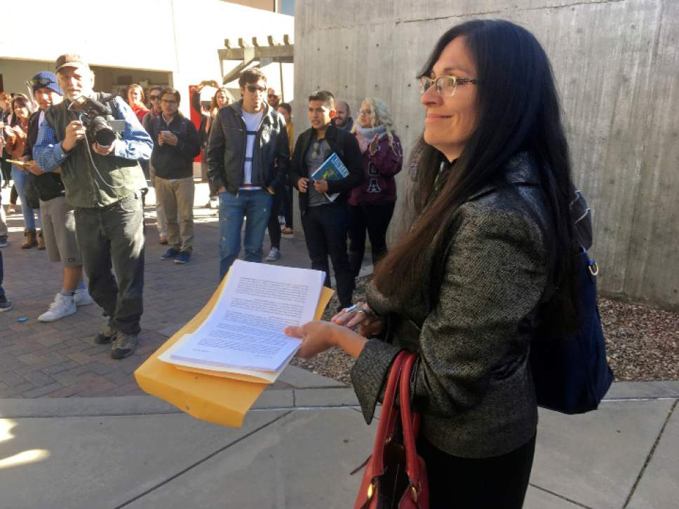 """FILE - In this Nov. 18, 2016 file photo, University of New Mexico Chicana and Chicano studies professor Irene Vasquez holds a letter with hundreds of signatures, asking school president Bob Frank to declare the campus a """"sanctuary university,"""" in Albuquerque, N.M. Universities and colleges in several states are considering labeling themselves """"sanctuary campuses"""" amid fears from immigrant students and pressure from activists following the election of Donald Trump. (AP Photo/Russell Contreras, File)"""