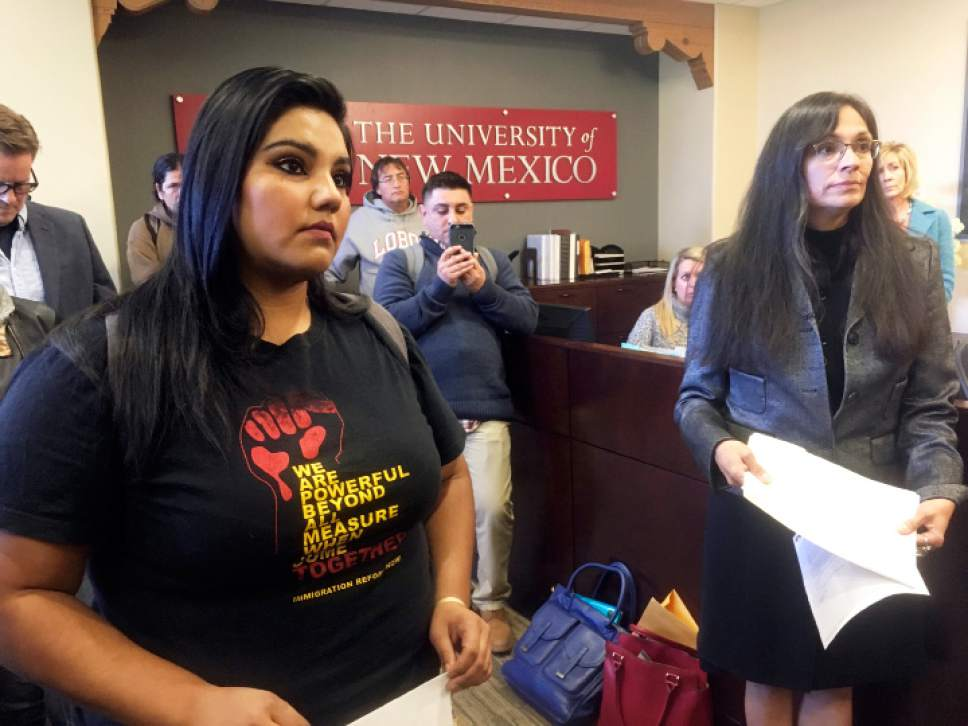 """FILE - In this Nov. 18, 2016 file photo, University of New Mexico student LuzHilda Campos, left, and Chicanaa and Chicano studies professor Irene Vasquez, right, present a letter with hundreds of signatures to school president Bob Frank, asking him to declare the campus a """"sanctuary university,"""" in Albuquerque, N.M. Universities and colleges in several states are considering labeling themselves """"sanctuary campuses"""" amid fears from immigrant students and pressure from activists following the election of Donald Trump. (AP Photo/Russell Contreras, File)"""
