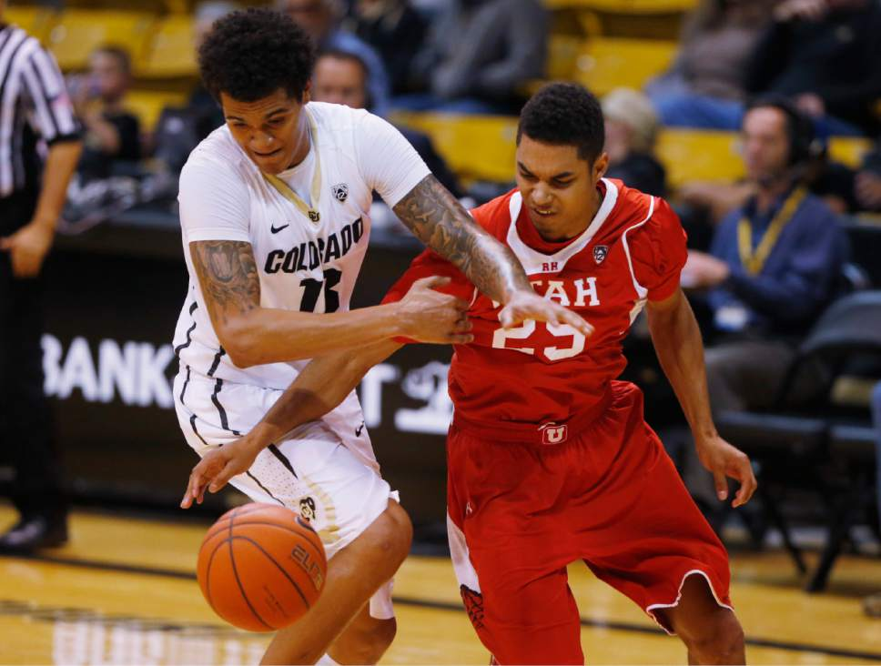 Colorado guard Dustin Thomas, left, battles for control of a loose ball with Utah guard Kenneth Ogbe in the second half of an NCAA college basketball game Saturday, Feb. 7, 2015., in Boulder, Colo. Utah won 79-51. (AP Photo/David Zalubowski)