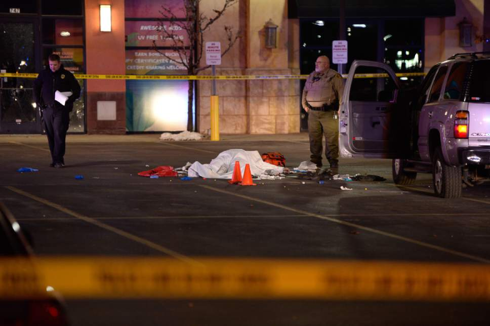 Francisco Kjolseth | The Salt Lake Tribune The body of a male suspect lies in the parking lot of the Cinemark in American Fork where he was shot at by police following brief pursuit on Sunday night, Dec. 4, 2014.  Police say he may have died from a self-inflicted gunshot. The suspect is believed to have just shot and killed a woman in her car by a Walmart nearby.