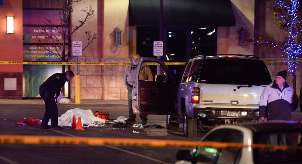 Francisco Kjolseth | The Salt Lake Tribune The body of a male suspect lies in the parking lot of the Cinemark in American Fork after he was shot at by police following a brief pursuit on Sunday night, Dec. 4, 2014. Police say he may have died from a self-inflicted gunshot. The suspect is believed to have just shot and killed a woman in her car by a Walmart nearby.
