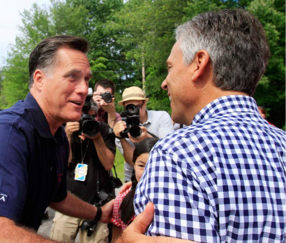 Republican presidential candidate, former Massachusetts Gov. Mitt Romney, left, greets fellow candidate, former Utah Gov. Jon Huntsman Jr., prior to the start the Fourth of July parade in Amherst, N.H., Monday, July 4, 2011. (AP Photo/Jim Cole)